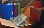 Tomas filing paperwork in a concertina file