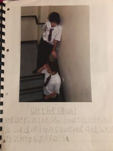 A photograph of Tom on the stairs in the school corridor with his written note of the correct corridor etiquette