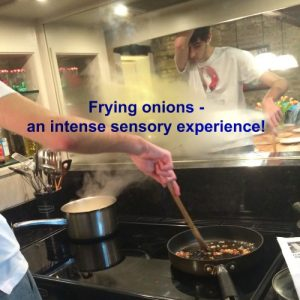 "Cooking skills, Tom cooking onions in a frying pan, steam coming off, wiping head. Text overlay ""frying onions - an intense sensory experience!"""